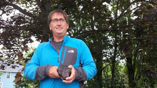Acadia University earth sciences professor Ian Spooner holds a piece of meteorite. He's been studying a crater in the Bloody Creek area of the Annapolis Valley.