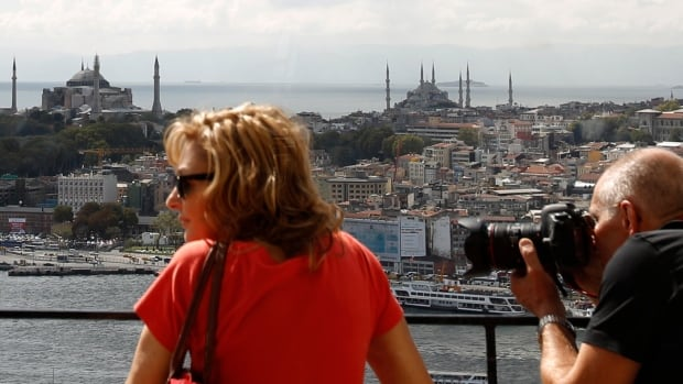Tourists, with the Hagia Sophia museum, left, and Blue Mosque, right, in the background, look at the old city from the historical Galata Tower in Istanbul. Turkey is going through economic upheaval, resulting in downward pressure on its currency, which could make a Canadian tourist's dollar go further there.