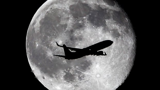 A United Airlines passenger plane crosses the waning gibbous moon, one day after a full moon on July 2, in Whittier, Calif. There are two full moons this month.