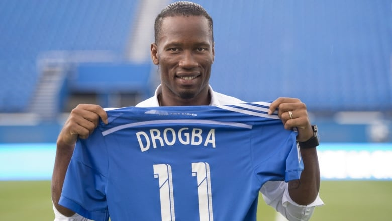 df14bdf9c Montreal Impact s newest player Didier Drogba holds up his new team jersey  following a news conference on Thursday in Montreal.