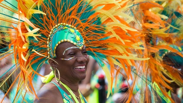 A parader shows off her costume while she walks in the Caribbean Carnival parade last year. An estimated one million people are expected to watch the colourful annual event today. (CBC)