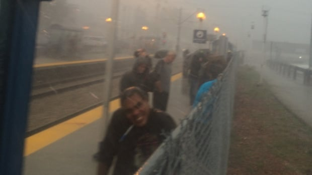 Commuters battle the elements while waiting for trains on August 4.