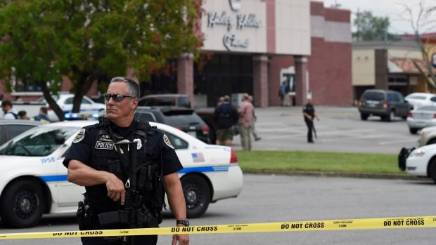 An officer stands in front of the movie theatre following an attack Wednesday in Antioch, Tenn., near Nashville. A man wielding a hatchet and a pellet gun inside the theatre was shot and killed by police.