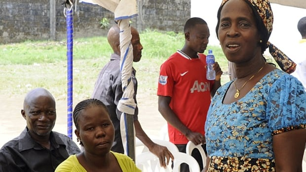 Beatrice Yordolo, who was declared a survivor of the Ebola virus on March 5, 2015, stands with family and neighbours on the outskirts of Monrovia, Liberia, in April. Researchers are starting to learn about the long-term complications among survivors.