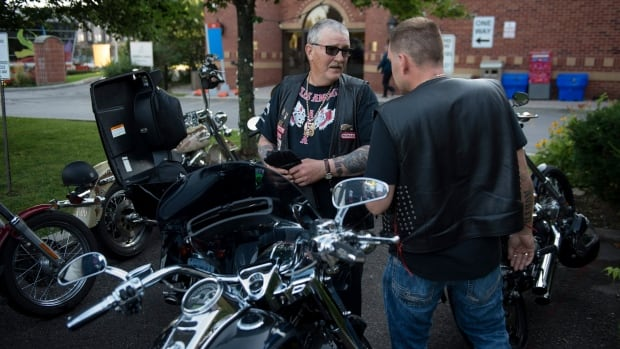 Members of various motorcycle clubs, including the Hells Angels, get their bikes ready outside a hotel Friday, Aug. 7, 2015 in Toronto. The group, in town to attend a funeral, were staying at the same hotel as Conservative Leader Stephen Harper and his family.