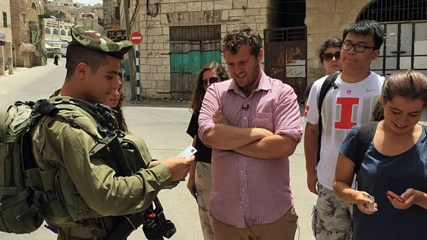 Extend tour leader Isaac Kates Rose, in pink shirt, assists Israeli soldiers checking the group members' IDs while in Hebron in the Israeli-occupied West Bank.