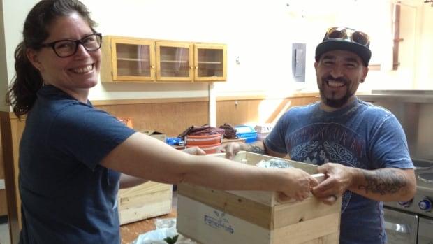 Food co-ordinator Alicia Lake hands customer Sebastian Belzile his box of produce.