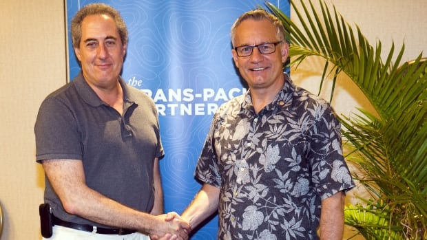 International Trade Minister Ed Fast, right, greets U.S. trade representative Michael Froman during meetings for the Trans-Pacific Partnership in Hawaii last month. A leaked draft of parts of the 12-country pact reveals Canada could be forced to bow to U.S. demands on copyright issues.