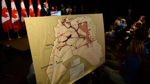 A map showing ISIS zones is displayed as Conservative Leader Stephen Harper speaks at a campaign stop in Ottawa on Aug. 9. Harper says if the Conservatives are re-elected this fall, his party would impose banned travel zones to combat terrorism.