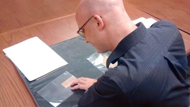 UBC professor Toph Marshall examines two small papyrus scraps which are believed to be the first of their kind in Western Canada.