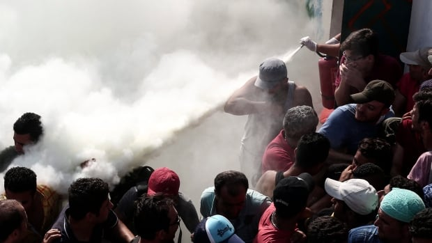 Policemen try to disperse hundreds of migrants by spraying them with fire extinguishers during a registration procedure at a stadium in the island town of Kos, Greece, on Tuesday