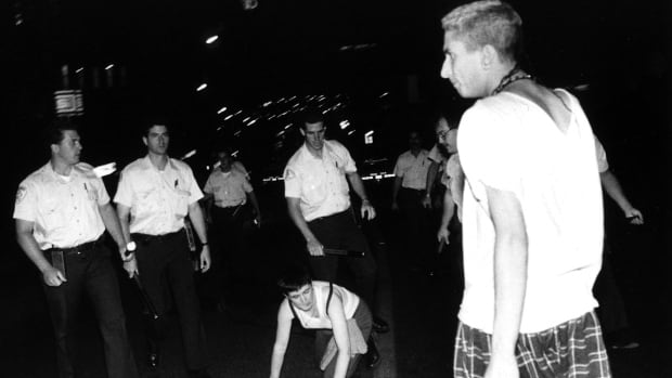 In this photo taken on July 15, 1990, two Sex Garage party-goers are seen interacting with members of the Montreal police.