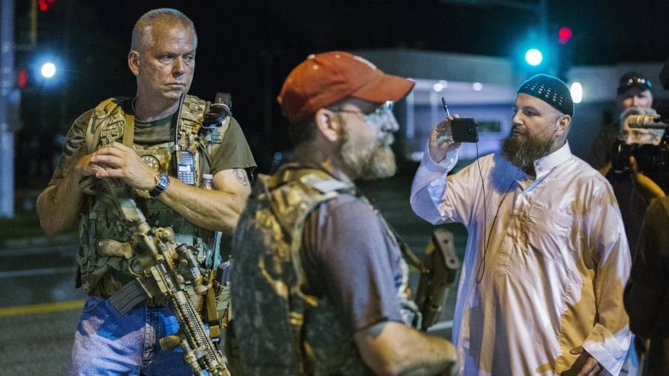 Members of the Oath Keepers walk with their personal weapons on the street during protests in Ferguson, Missouri