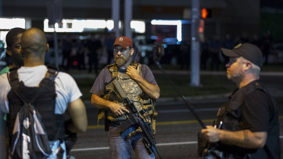 Members of the Oath Keepers walk with their personal weapons on the street during protests in Ferguson, Missouri August 11, 2015. Police in riot gear clashed with protesters who had gathered in the streets of Ferguson early on Tuesday to mark the anniversary of the police shooting of an unarmed black teen whose death sparked a national outcry over race relations. REUTERS/Lucas Jackson  - RTX1NUGS