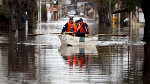 Argentine policemen patrol a flooded street on a boat in Lujan, Argentina, August 12, 2015. Torrential rains linked to El Nino last weekend caused rivers to rise and flood cities in northern Buenos Aires province.
