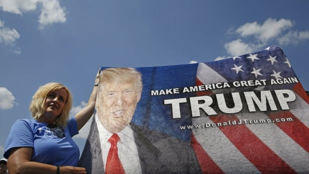 A supporter of U.S. Republican presidential hopeful Donald Trump holds a banner for his arrival near the Iowa State Fair in Des Moines on Saturday.