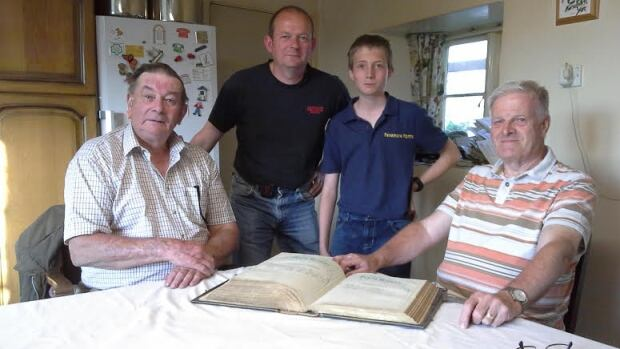 From left: George Fenemore, his son Chris, his grandson Ben and historian John Webb with the recovered family Bible.