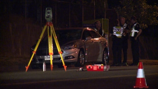 Police investigators stand near a damaged car after a pedestrian was struck on SE Marine Drive Wednesday night in Vancouver.