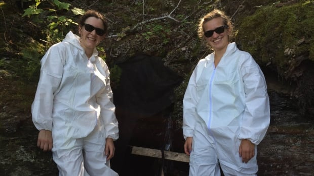 Kaleigh Norquay (l) and Erin Segstro, researchers from the University of Winnipeg, stand outside a cave about 20 minutes west of Thunder Bay. They recently carried out equipment tests ahead of a night of swabbing and tagging bats.