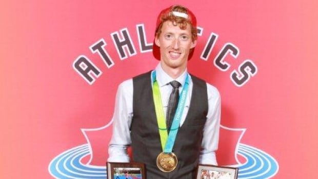 Canadian race walker Evan Dunfee with his Pan Am gold medal and other awards.