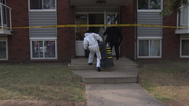 Forensics officers in white suits were seen entering the building where the woman was found dead Tuesday morning.