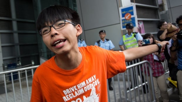 Student activist Joshua Wong talks to members of the media before reporting to the Wanchai Police Station in Hong Kong on Thursday.