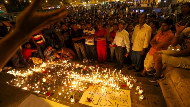 Migrants attend a candlelight ceremony at a Budapest railway station in memory of 71 refugees who died in a truck found in Austria on Thursday.