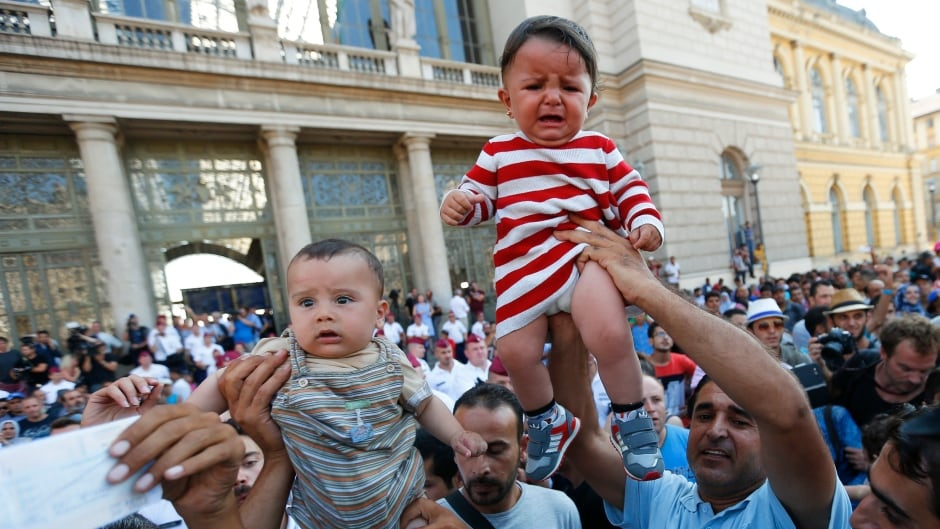 Migrants wave their train tickets and lift up children outside the main Eastern Railway station in Budapest, Hungary, September 1, 2015. The issue of what Canada should do to help alleviate the crisis of refugees and other desperate migrants in Europe was raised on the campaign trail in Canada Wednesday.