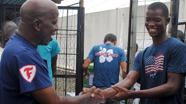 Cassius Kollie (right), receives a certificate for being cured of Ebola in Paynesville, Liberia, in July.
