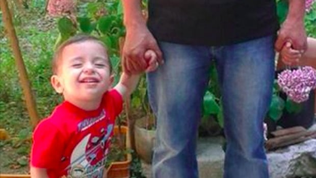 An undated photo of Alan Kurdi holding his father's hand was sent to Buzzfeed reporter Hussein Kesvani by a family friend.