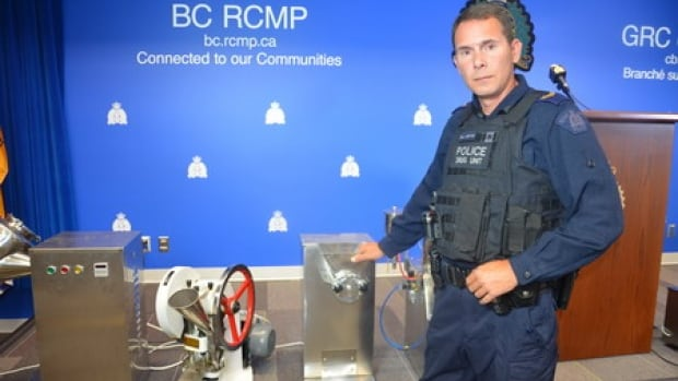 Corporal Derek Westwick of the RCMP shows the equipment taken from a Burnaby fentanyl pill production facility.