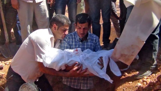 Abdullah Kurdi holds the body of his three-year-old son Alan during a funeral service in Syria, on Sept. 4.