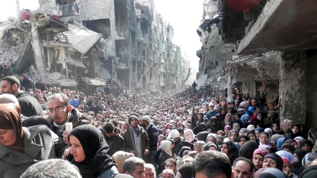 Residents of the besieged Palestinian camp of Yarmouk, queuing to receive food supplies, in Damascus, Syria  on Jan. 31, 2014.