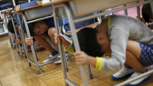 School children take shelter under desks during an earthquake simulation exercise at an elementary school in Tokyo September 1, 2015.