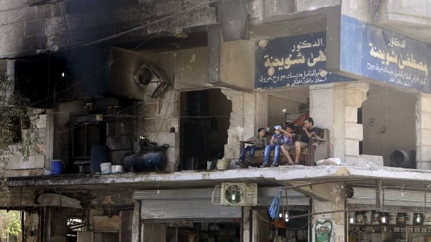 Residents sit on a couch on a balcony of a damaged building in Aleppo's al-Shaar neighborhood.