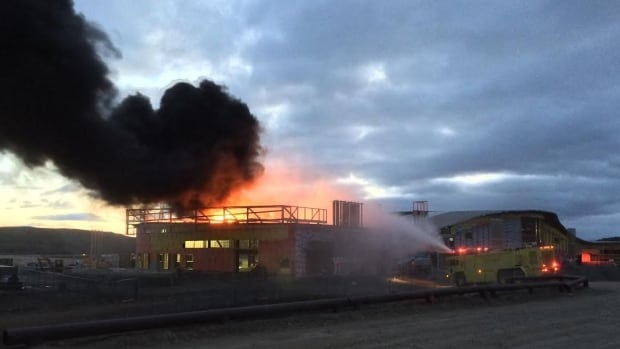 A fire truck sprays water on Iqaluit's new airport terminal building, which caught fire Saturday.