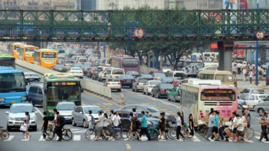 Pedestrians cross the road past heavily congested traffic in the town centre in Guangzhou in the southern Chinese province of Guangdong.
