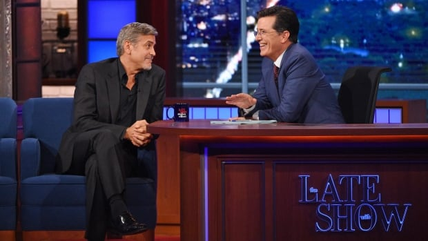 Stephen Colbert, right, chats with actor George Clooney during the first episode of The Late Show on Tuesday. Clooney and Republican presidential candidate Jeb Bush were the guests for Colbert's debut.