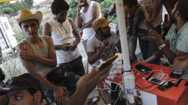 Migrants from Syria charge their phones outside a refugee camp on the Greek island of Lesbos last month. Recognizing that smartphones have become essential lifelines for many asylum-seekers, the UN has handed out 33,000 SIM cards and tens of thousands of solar-powered chargers at refugee camps.
