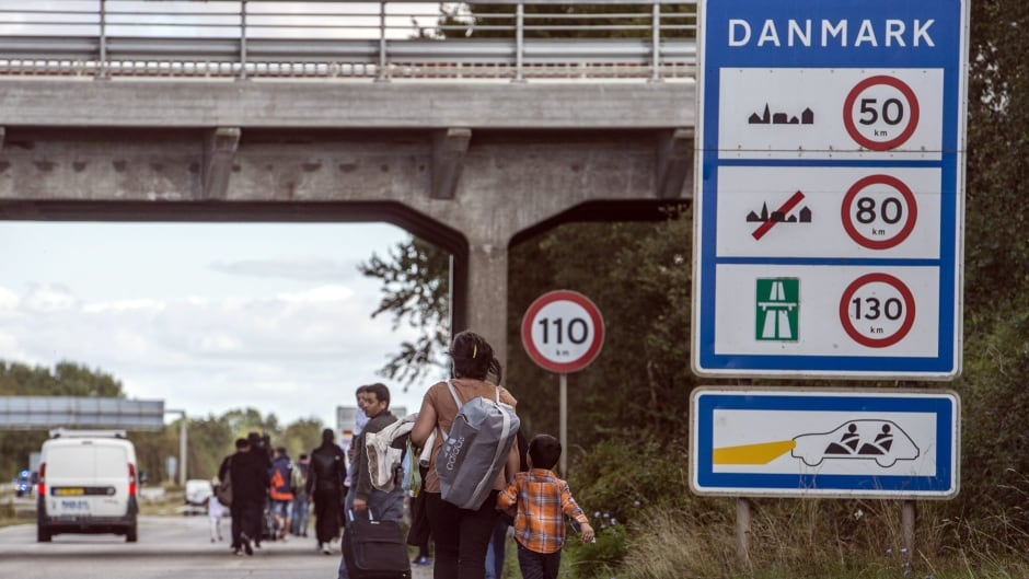 Migrants, who came from Germany by ferry and train Sunday night, walk  from Rodby in southern Denmark towards Sweden on Monday Sept. 7, 2015. Most of the migrants came from Syria, and  wished to continue to Sweden where they will seek asylum.