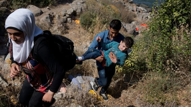 Syrian refugees walk up a hill as they arrive on a dinghy after crossing from Turkey to Lesbos island, Greece, Friday, Sept. 11, 2015.