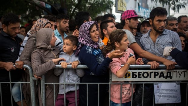 Syrian refugees wait to be registered by police in the southern Serbian town of Presevo, Friday, Sept. 11, 2015. Canada has announced a Syrian emergency relief fund that will match donations from Canadians up to $100 million.