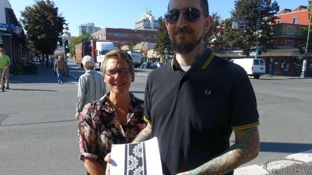 Teri Hustins from the Fort Street Business Association and tattoo artist Gerry Kramer show off the tattoo that he designed for the crosswalk.