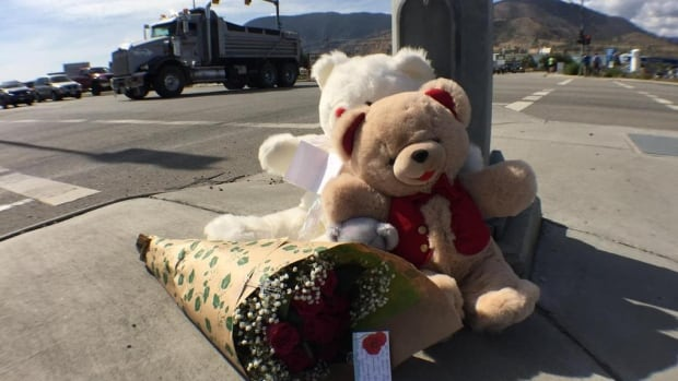 Two teddy bears and a bouquet of flowers sit on the sidewalk near the Penticton intersection where James McIntosh was struck by a car on Tuesday evening.
