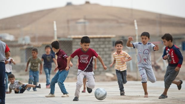 Children play soccer at Kawergosk a camp for Syrian refugees in the Kurdish region of northern Iraq. About half of the 10,000 people living in the two-year-old settlement are children.
