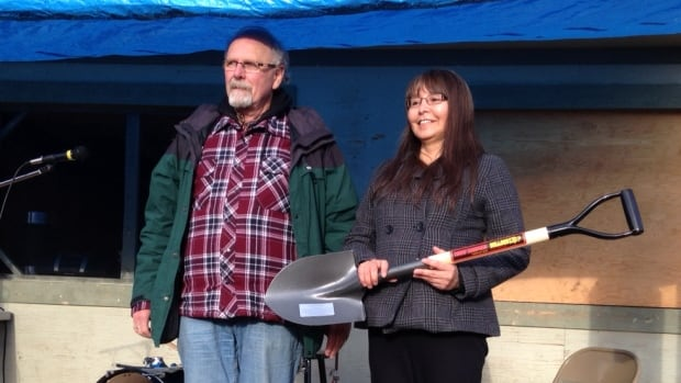 Yukon College vice president Chris Hawkins, left, and Tr'ondëk Hwëch'in First Nation chief Roberta Joseph pose with a ceremonial shovel presented to the First Nation to mark the first harvest at their Dawson City teaching farm.