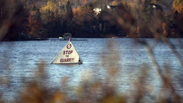 ​A sign protesting the proposed quarry has been floating in Miller Lake for years.
