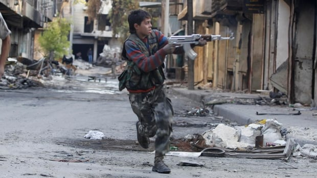 Mohammad, a 13 year-old fighter from the Free Syrian Army, aims his weapon as he runs from snipers loyal to the Syrian regime in Aleppo's Bustan al-Basha district October 29, 2013. Mohammad joined the Free Syrian Army after his father died during clashes with the Syrian regime. The gun he is using was his father's.