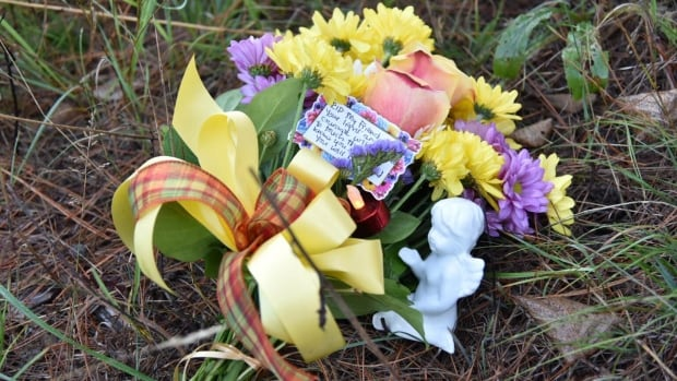 A bouquet of flowers sits near a home on Szczipior Road in Wilno, Ont., where the body of Anastasia Kuzyk was found on Tuesday morning.
