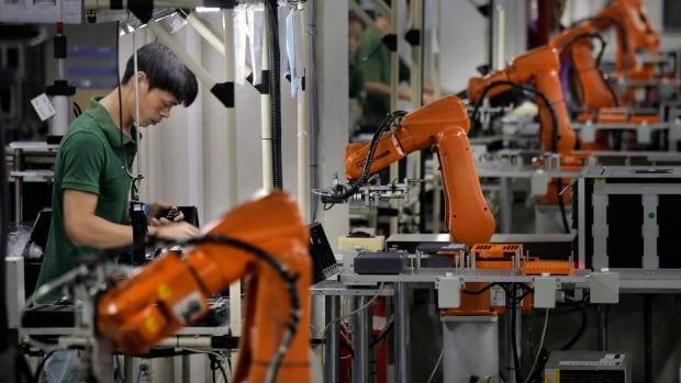 A worker at Shenzhen Rapoo Technology Co. in southern China toils alongside orange robotic arms that assemble computer mice and keyboards. The company installed 80 of the robots five years ago, allowing it to trim its workforce by two-thirds.